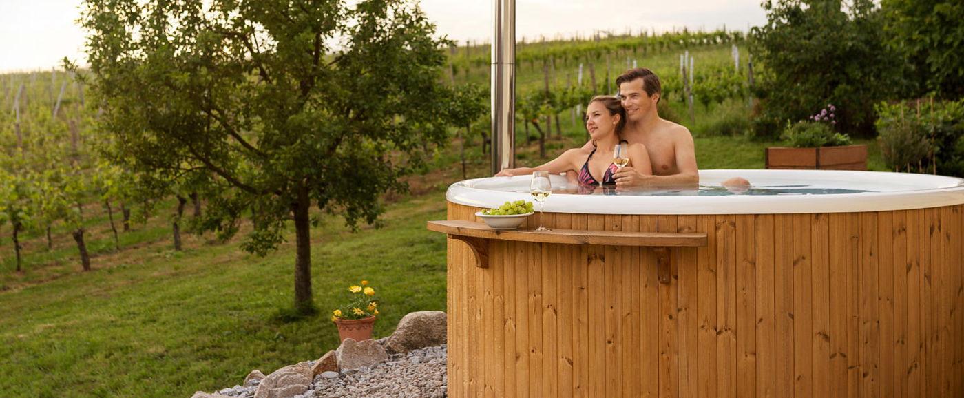 Ett par sitter i Skärgårdstunnan Regal i en trädgård bredvid en vinodling
