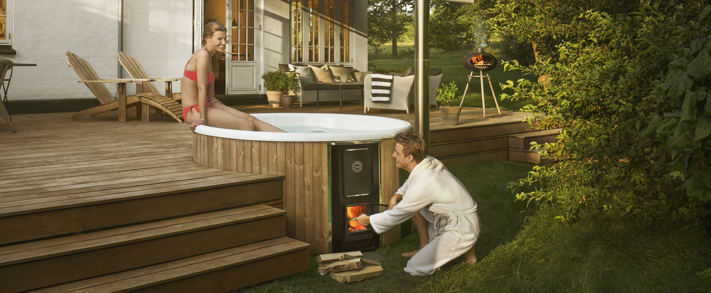 A woman sits on the edge of a Skargards Regal that is build in a wooden terrace of danish garden, while a man is firing up the stove of the hot tub.