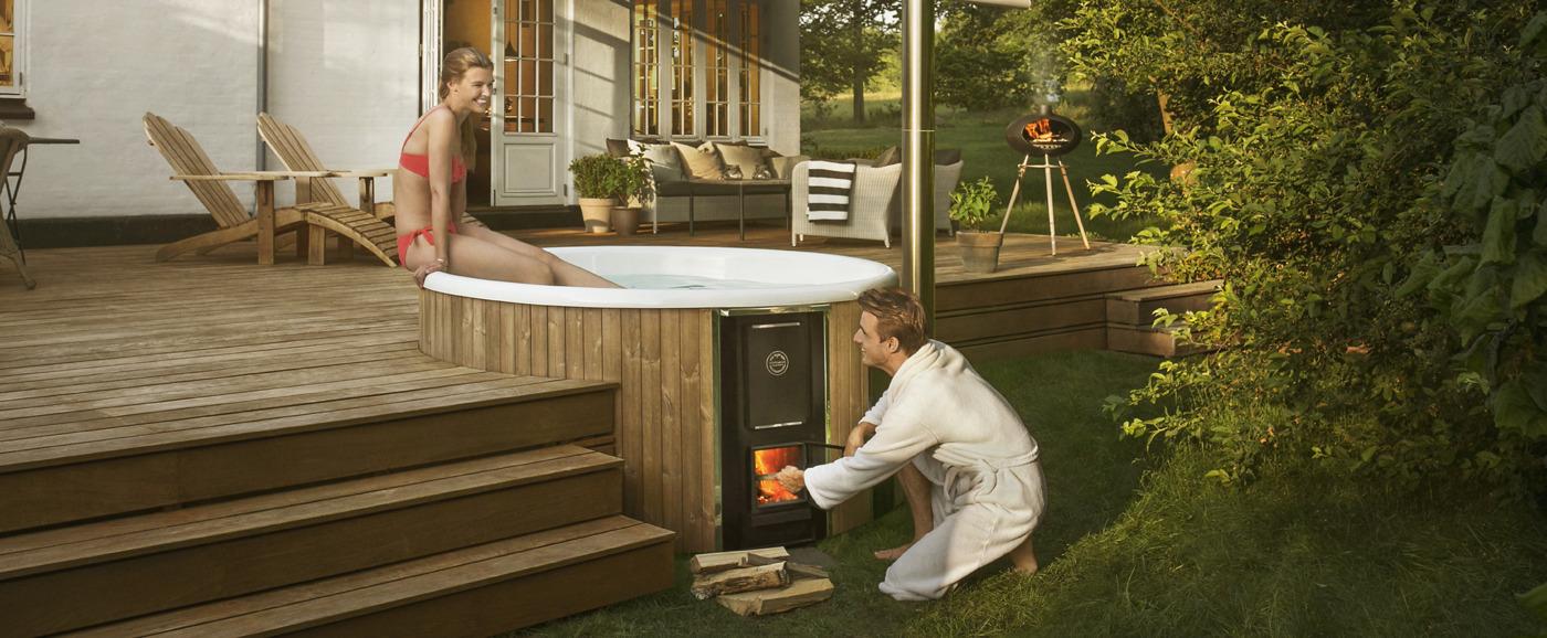 Una donna siede sul bordo di una vasca Skargards Regal incassata in una terrazza in legno di un giardino danese, mentre un uomo accende la stufa della vasca idromassaggio.