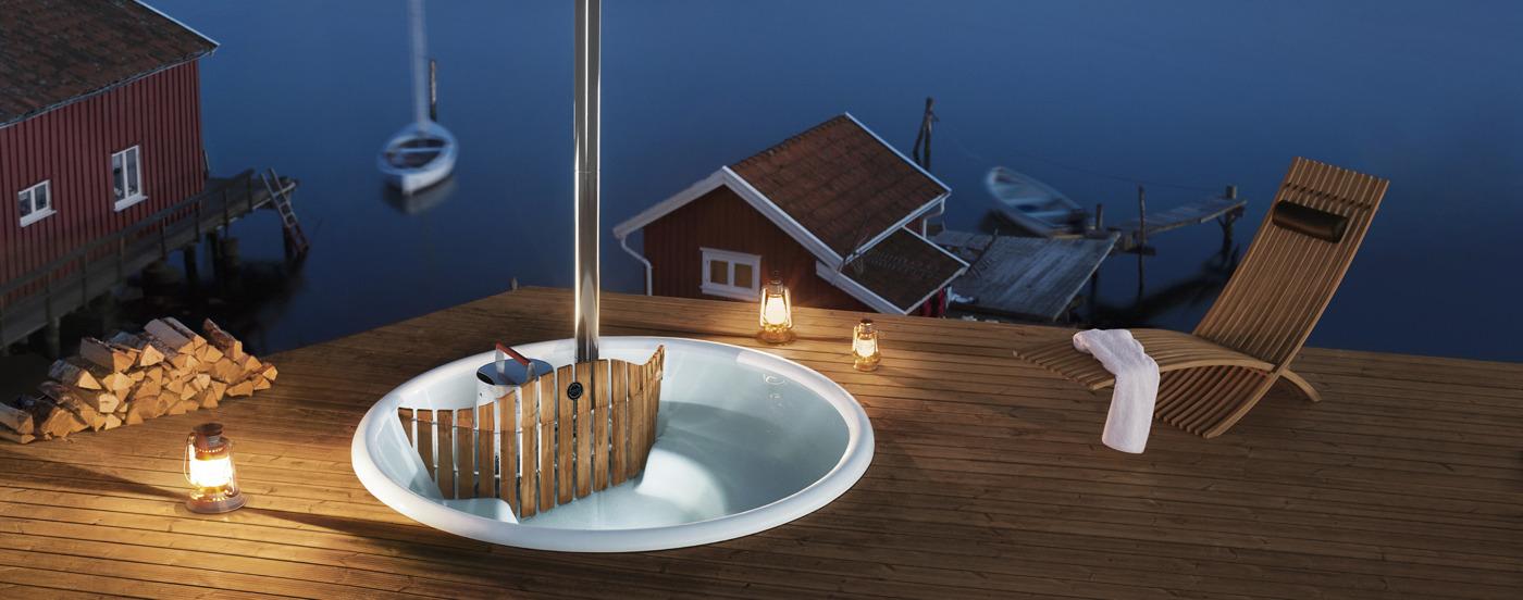 Eine Nachtaufnahme des Badebottichs Terrass, welcher in eine Holzterrasse eingebaut wurde und von Lampen beleuchtet wird