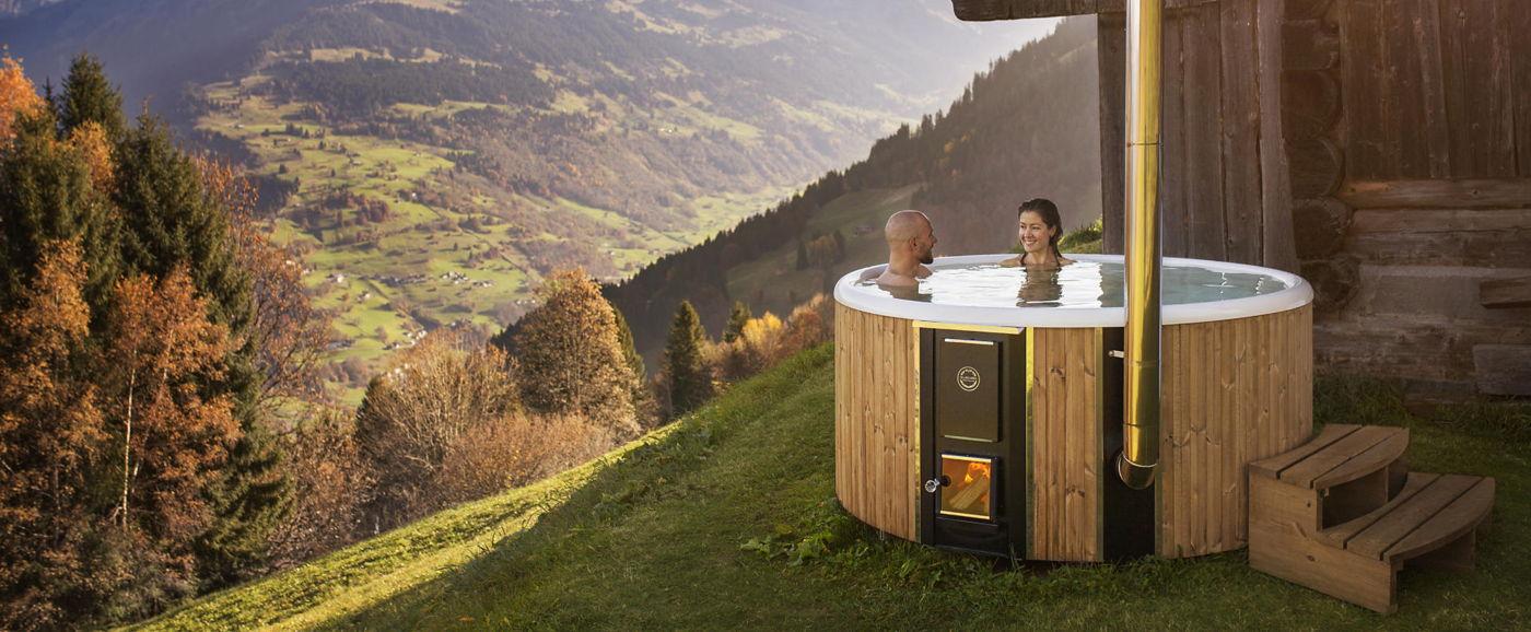 Nainen ja mies vuoristossa nauttimassa kylvystä puulämmitteisessä Skargards Regal -kylpytynnyrissä.