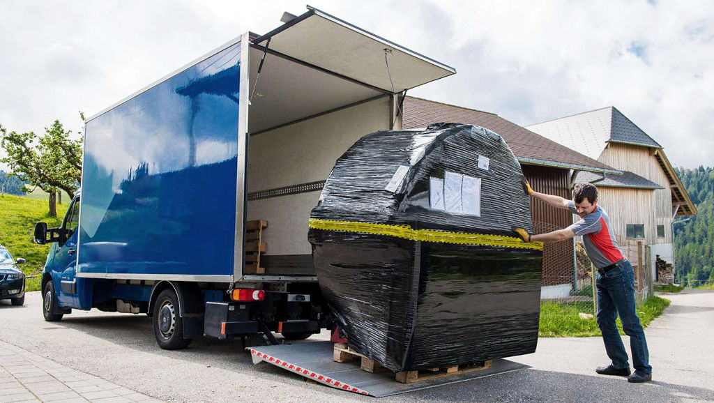 A packaged hot tub standing on a tail lift of a truck.