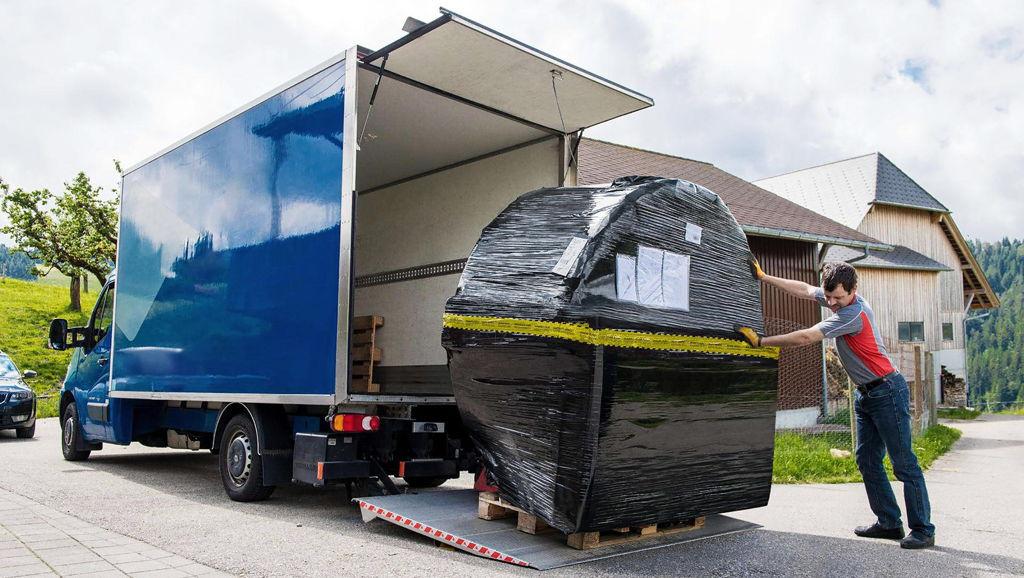 Ein LKW mit heruntergefahrener Hebebühne, auf der ein verpackter Hot Tub steht