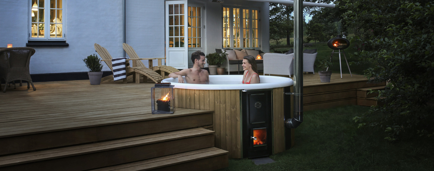 An evening shot of the wood-fired hot tub Regal that is build in a wooden terrace in front of a house with a couple inside