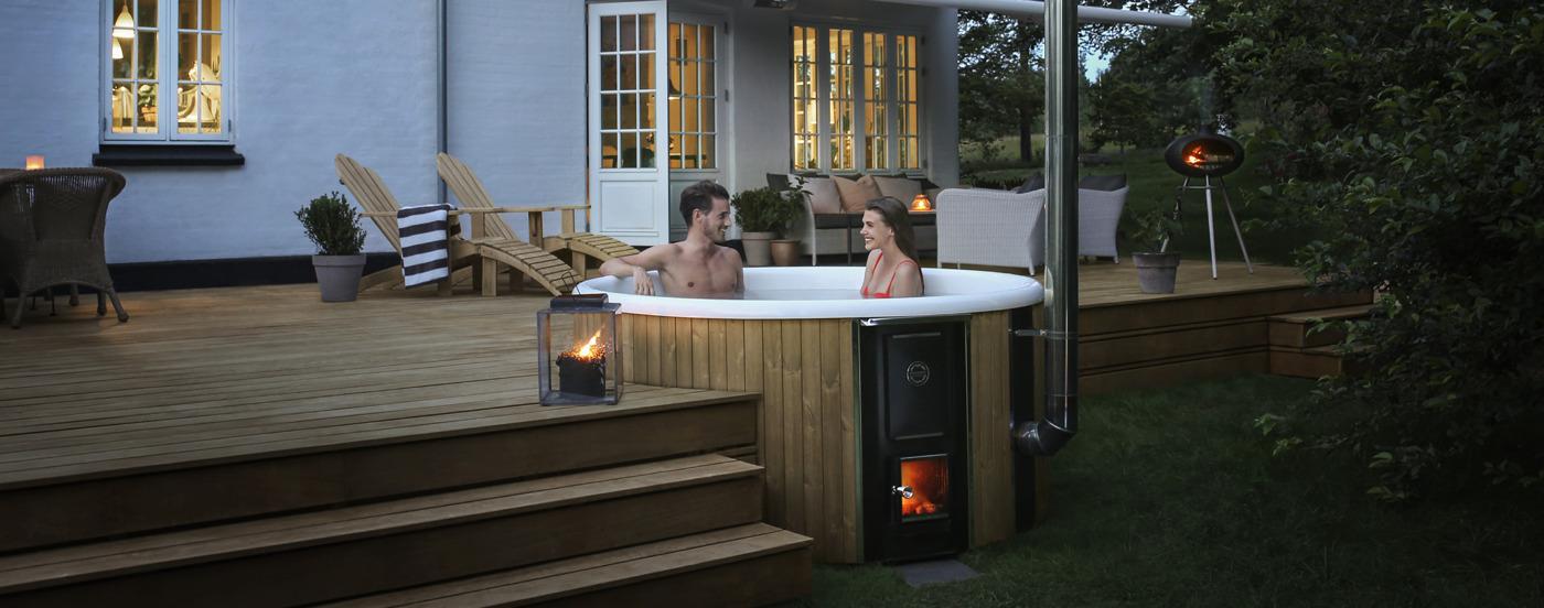 Uno scatto serale della vasca riscaldata a legna Skargards Regal incassata in una terrazza in legno di fronte a una casa con una coppia all'interno