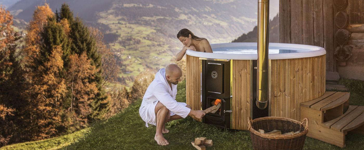 Nainen istuu Skargards Regal -kylpytynnyrin sisällä ja katsoo kamiinaan tulta sytyttävää miestä.