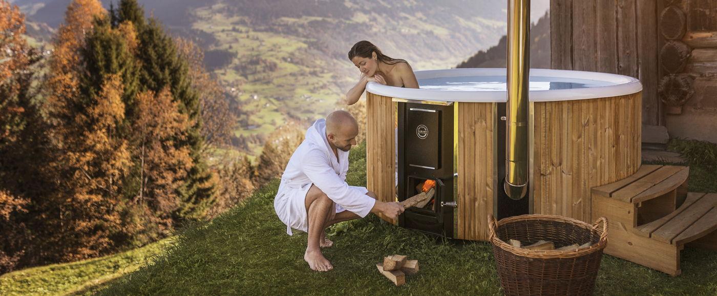 Una donna seduta all'interno della vasca idromassaggio Regal mentre guarda un uomo che accende la stufa