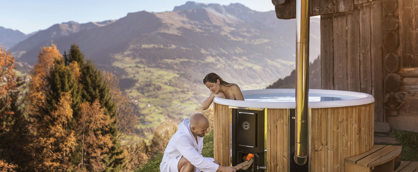 A women sitting inside the Skargards Regal hot tub and looking at a man that is firing up the stove