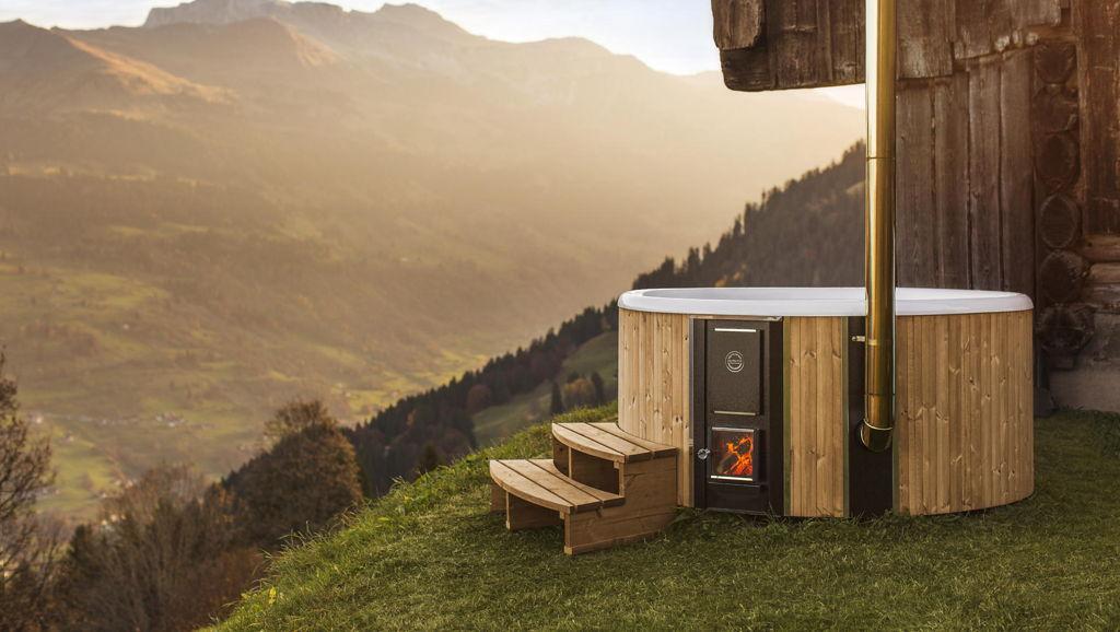 La vasca da esterno a legna Skargards Regal posizionata vicino a una casetta in legno sulle montagne svizzere