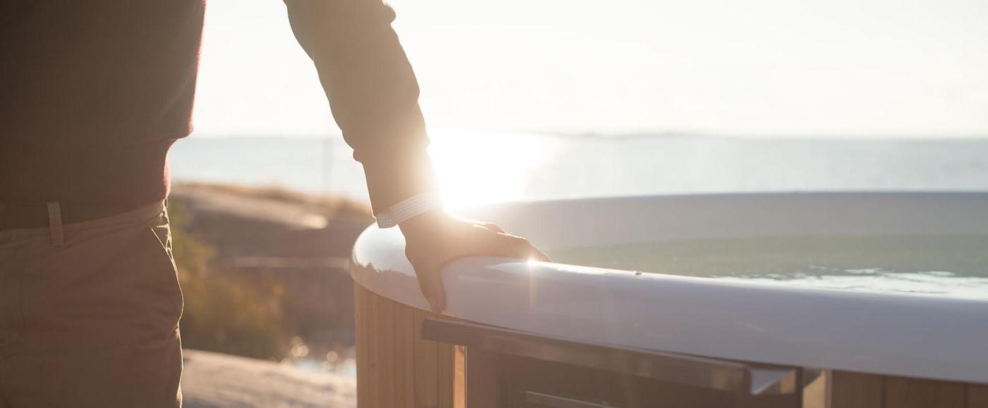 Nærbilde av en manns hånd som holder på kanten av karet til Skargards Regal badestamp plast