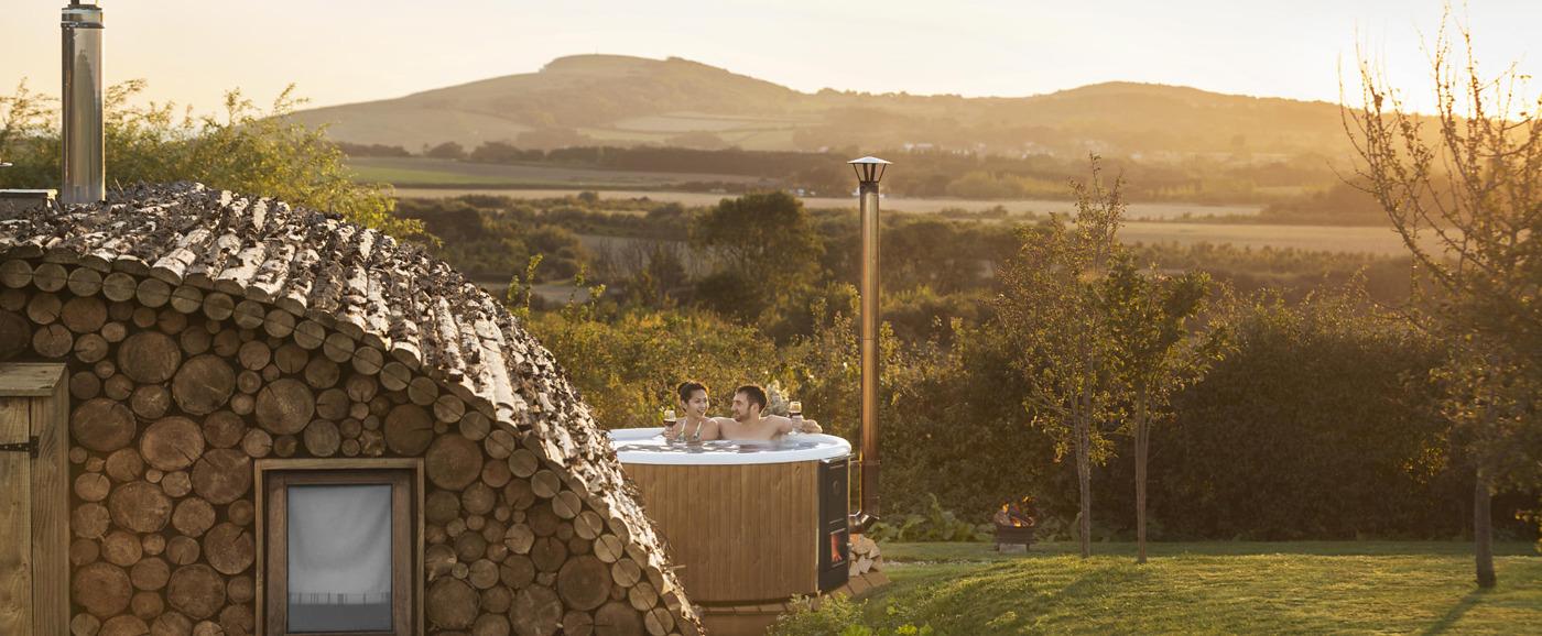 Et par nyter livet i den vedfyrte badestampen Skargards Regal ved siden av en tømmerhytte på et glampingsted i Storbritannia