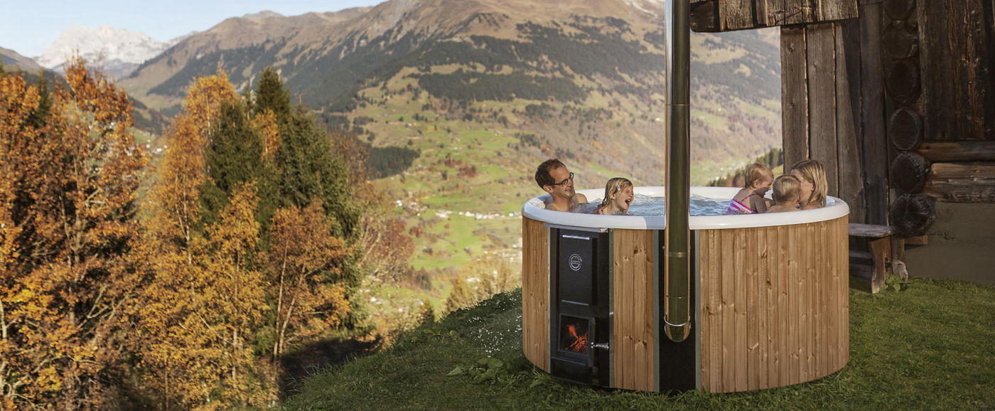 A family enjoys a bath in the Skargards Regal wood-burning hot tub in the Swiss mountains