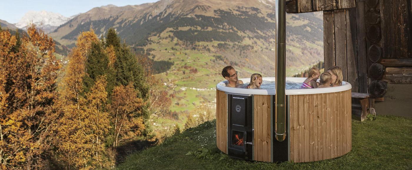 En familj njuter av ett bad i Skärgårdstunnan Regal vedeldad badtunna plast i de schweiziska alperna