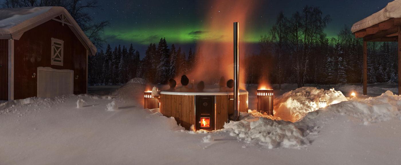 Eine Gruppe sitzt bei Nacht in dem Badezuber Rojal und blickt auf die Nordlichter am Himmel.