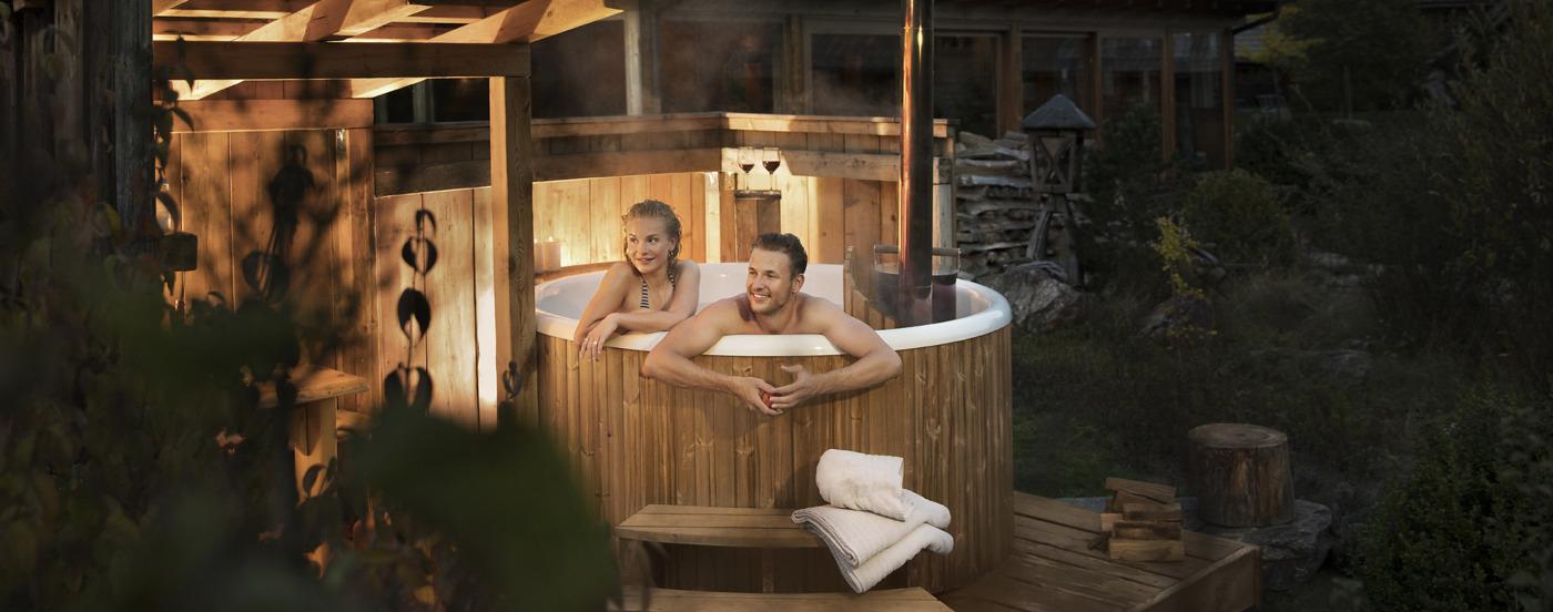 Een nachtfoto van het houten hottub met daarin een man en een vrouw die de omgeving observeren
