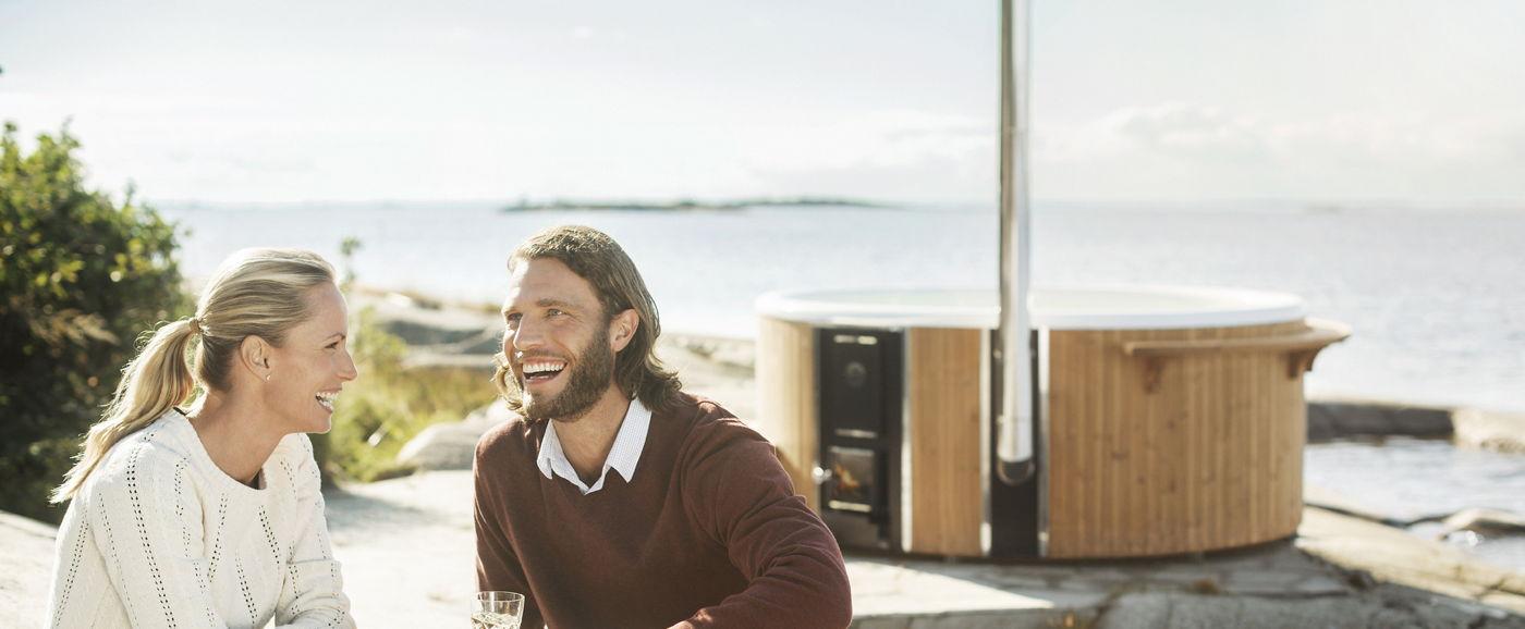 Un homme souriant parle avec sa femme avec un bain nordique Skargards en arrière-plan.