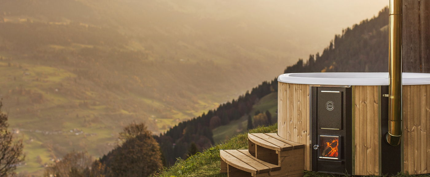 The Skargards Regal wood-burning hot tub placed next wo a wooden house in the Switzerland mountains