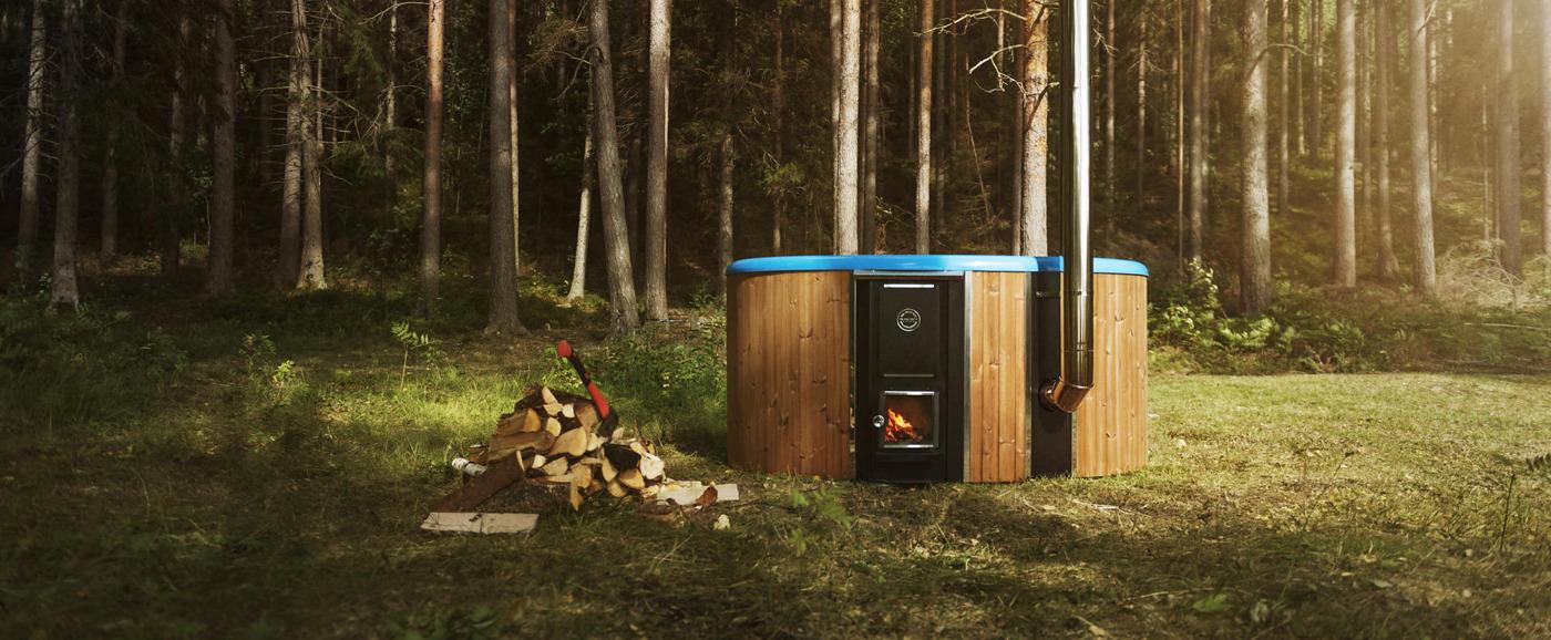 Das Badefass Rojal mit einer blauen Wanne platziert in einem Waldstücken neben einem Stapel Holz