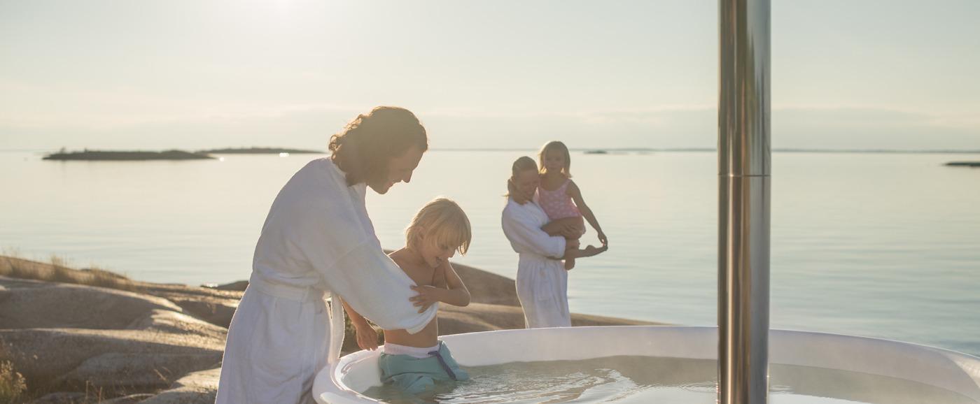 En man lyfter i en pojke i Skärgårdstunnans vedeldade badtunna Regal medan en kvinna och en flicka går mot badet