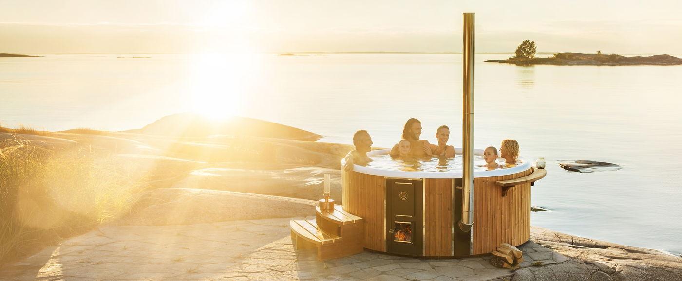 Overzichtsfoto van een houtgestookte hottub Skargards Rojal, badend met een gezin bij zonsondergang op een stenen platform naast een meer in Zweden