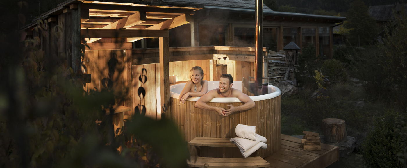 Night picture of the wooden hot tub Skargards Panel with a couple inside at Landgut Moserhof