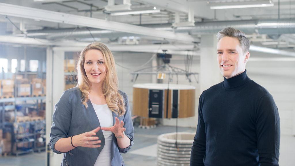 Skärgårdstunnans medarbetare Jana och Erik står i fabriken framför en upphissad badtunna